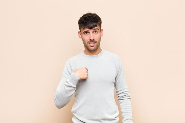 Jeune bel homme se sentant confus, perplexe et peu sûr, pointant vers soi se demandant et demandant qui, moi? sur un mur chaud
