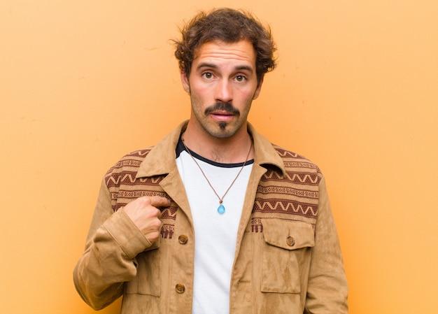 Jeune bel homme se sentant confus, perplexe et peu sûr, pointant vers soi se demandant et demandant qui, moi? sur le mur orange