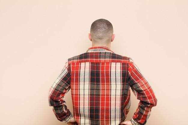 Jeune bel homme se sentant confus ou plein ou des doutes et des questions, se demandant, avec les mains sur les hanches, vue arrière contre le mur plat