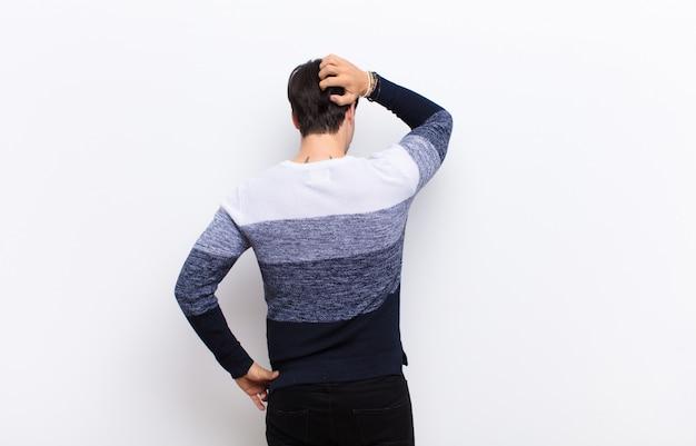 Jeune bel homme se sentant désemparé et confus, pensant à une solution, avec la main sur la hanche et d'autres sur la tête, vue arrière contre le mur blanc