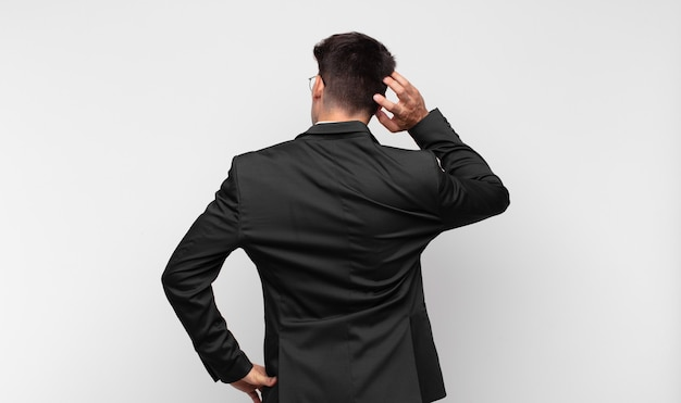 Jeune bel homme se sentant désemparé et confus, pensant à une solution, avec la main sur la hanche et d'autres sur la tête, vue arrière