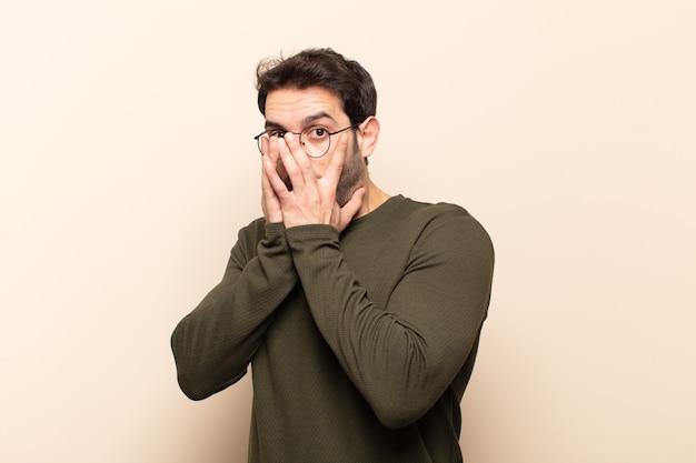 Jeune bel homme se sentant effrayé ou embarrassé, furtivement ou espionnage avec les yeux à moitié couverts de mains