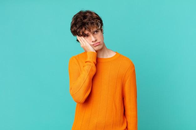Jeune bel homme se sentant ennuyé, frustré et somnolent après une période fastidieuse
