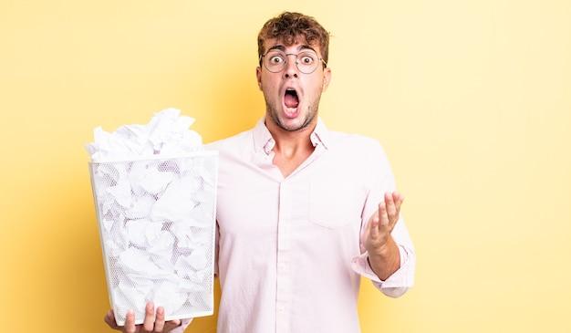 Jeune bel homme se sentant extrêmement choqué et surpris. concept de poubelle de boules de papier