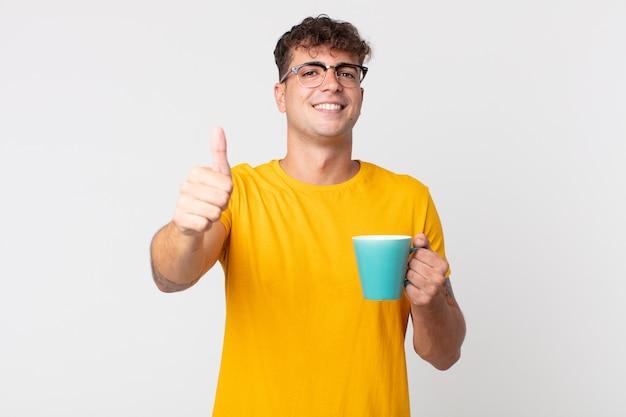 Jeune bel homme se sentant fier, souriant positivement avec les pouces vers le haut et tenant une tasse de café