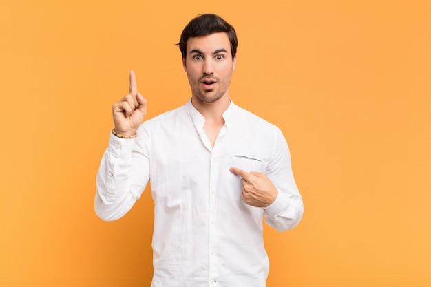 Jeune bel homme se sentant fier et surpris, pointant vers soi avec confiance, se sentant comme le succès numéro un