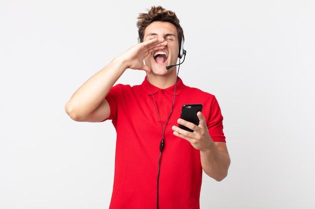 Jeune bel homme se sentant heureux, donnant un grand cri avec les mains à côté de la bouche avec un smartphone et un casque