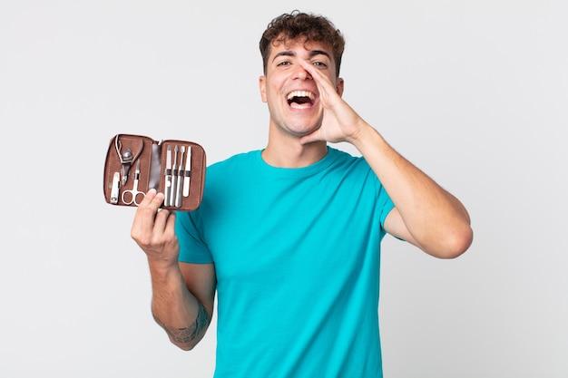Jeune bel homme se sentant heureux, donnant un grand cri avec les mains à côté de la bouche et tenant un étui à outils à ongles