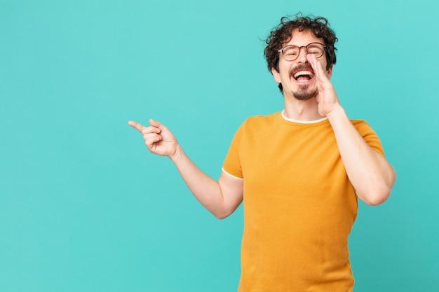 Jeune bel homme se sentant heureux, donnant un grand cri avec les mains à côté de la bouche