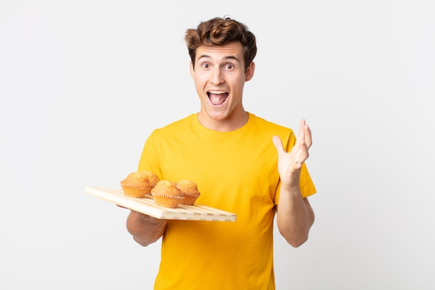 Jeune bel homme se sentant heureux et étonné de quelque chose d'incroyable tenant un plateau à muffins