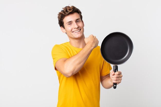 Jeune bel homme se sentant heureux et face à un défi ou célébrant et tenant une casserole