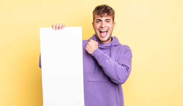 Jeune bel homme se sentant heureux et faisant face à un défi ou célébrant. concept d'espace de copie