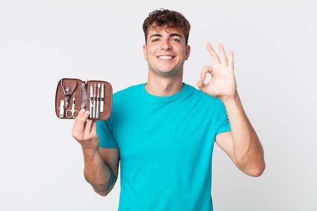 Jeune bel homme se sentant heureux, montrant son approbation avec un geste correct et tenant un étui à outils à ongles