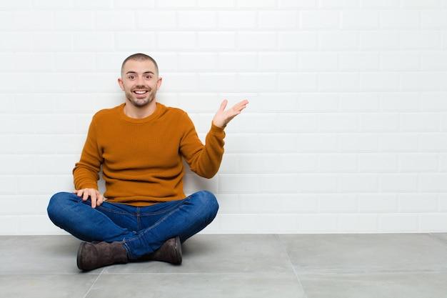 Jeune bel homme se sentant heureux, surpris et joyeux, souriant avec une attitude positive, réalisant une solution ou une idée assis sur le sol