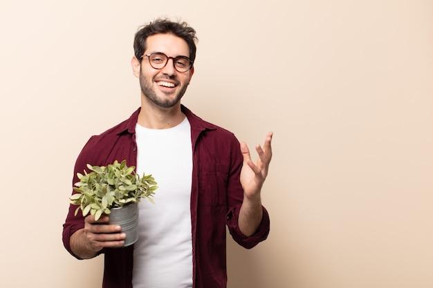 Jeune bel homme se sentant heureux, surpris et joyeux, souriant avec une attitude positive, réalisant une solution ou une idée
