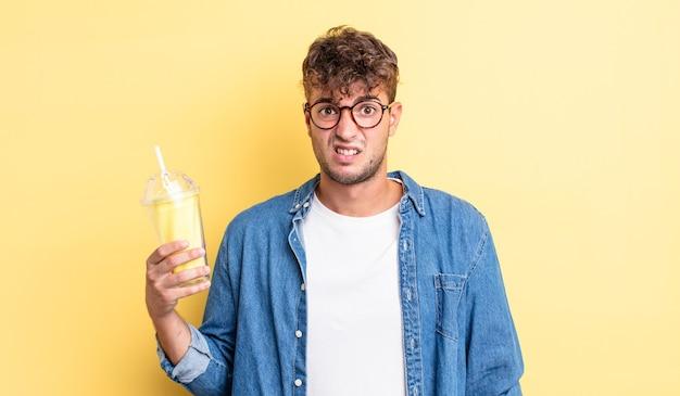 Jeune bel homme se sentant perplexe et confus. concept de milk-shake