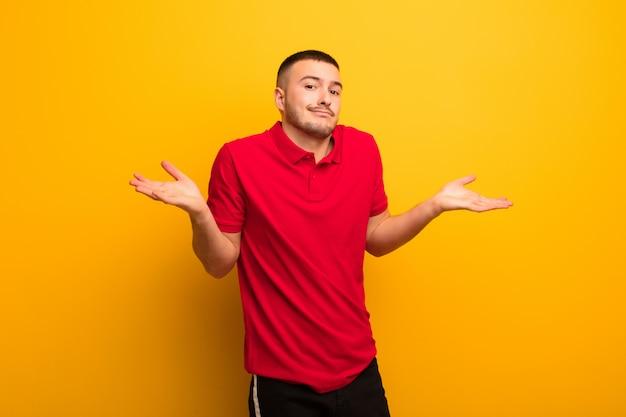 Jeune bel homme se sentant perplexe et confus, doutant, pondérant ou choisissant différentes options avec une drôle d'expression contre un mur plat
