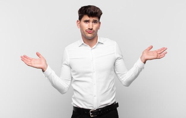 Jeune bel homme se sentant perplexe et confus, doutant, pondérant ou choisissant différentes options avec une expression drôle