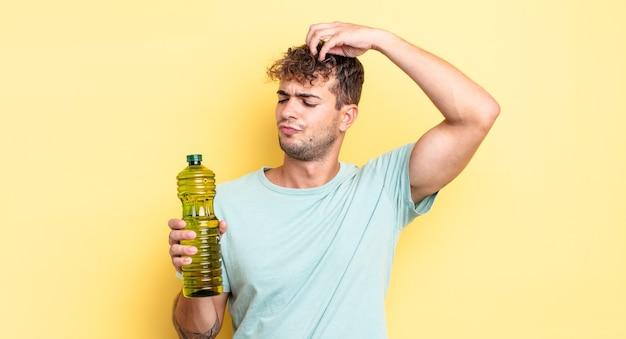 Jeune bel homme se sentant perplexe et confus, se grattant la tête. concept d'huile d'olive