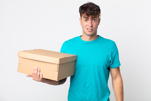 Jeune bel homme se sentant perplexe et confus et tenant une boîte en carton