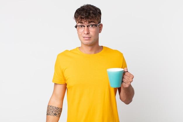 Jeune bel homme se sentant perplexe et confus et tenant une tasse de café