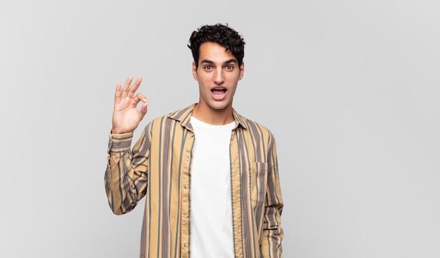 Jeune bel homme se sentant réussi et satisfait, souriant avec la bouche grande ouverte, faisant signe correct avec la main