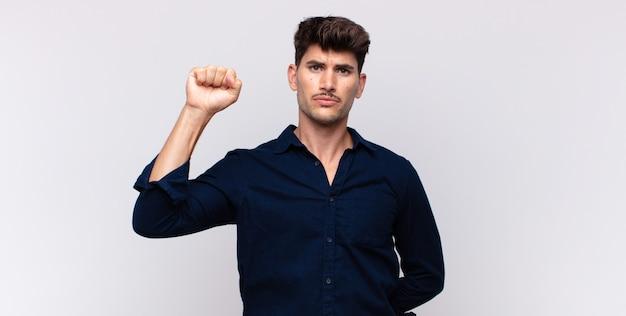 Jeune bel homme se sentant sérieux, fort et rebelle, levant le poing, protestant ou luttant pour la révolution