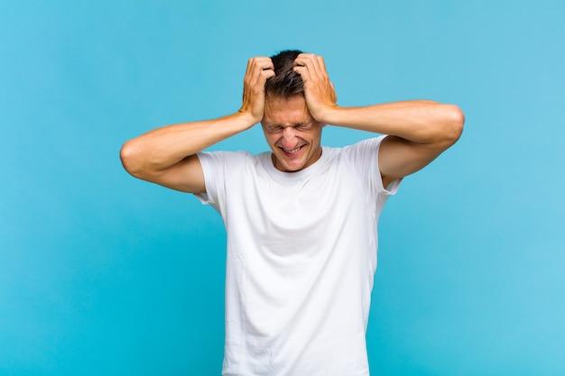 Jeune bel homme se sentant stressé et frustré, levant les mains à la tête, se sentant fatigué, malheureux et souffrant de migraine
