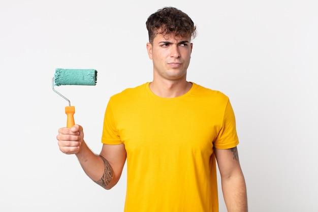 Jeune bel homme se sentant triste, contrarié ou en colère et regardant sur le côté. concept de maison de peinture