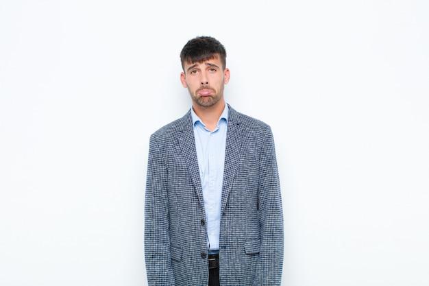 Jeune bel homme se sentant triste et stressé, bouleversé à cause d'une mauvaise surprise, avec un regard négatif et anxieux contre le mur blanc