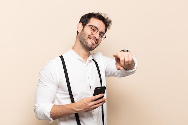 Jeune bel homme se sentir heureux et confiant, pointant vers la caméra avec les deux mains et en riant, en vous choisissant