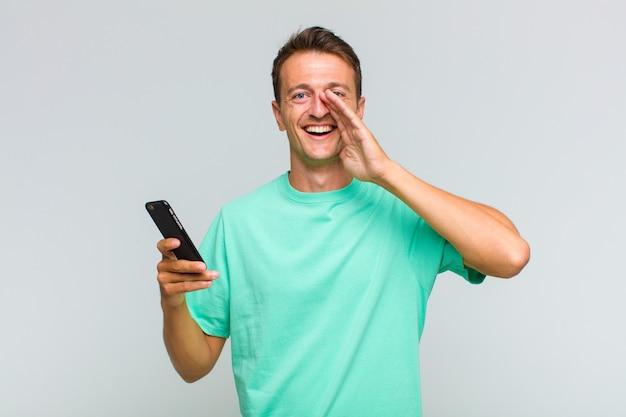 Jeune bel homme se sentir heureux, excité et positif, donnant un grand cri avec les mains à côté de la bouche, appelant