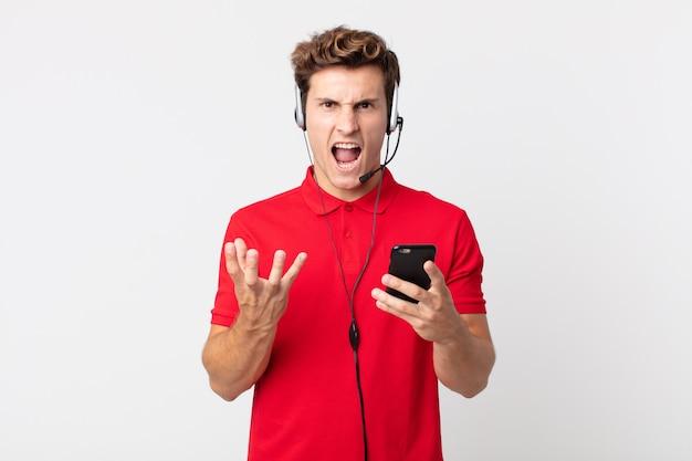 Jeune bel homme semblant en colère, agacé et frustré par un smartphone et un casque