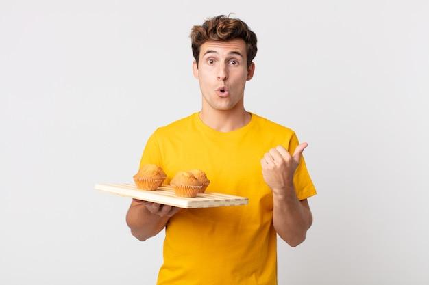 Jeune bel homme semblant étonné d'incrédulité tenant un plateau à muffins