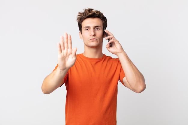 Jeune bel homme semblant sérieux montrant la paume ouverte faisant un geste d'arrêt et parlant avec un téléphone intelligent