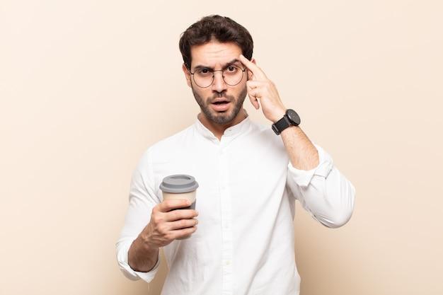 Jeune bel homme semblant surpris, bouche bée, choqué, réalisant une nouvelle pensée, idée ou concept