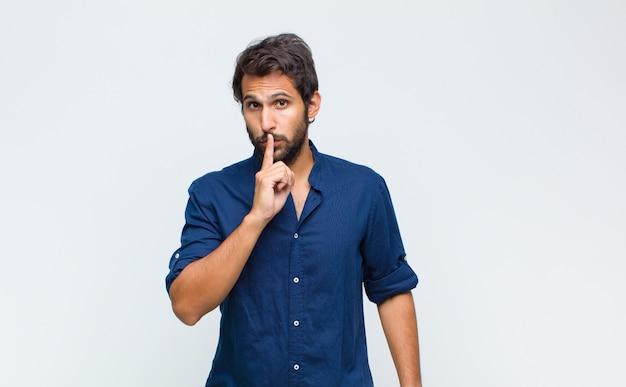Jeune bel homme à la sérieuse et mécontent avec les deux doigts croisés à l'avant dans le rejet, demandant le silence