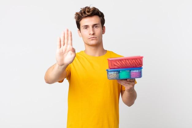Jeune bel homme à la sérieuse montrant la paume ouverte faisant un geste d'arrêt et tenant des boîtes à lunch