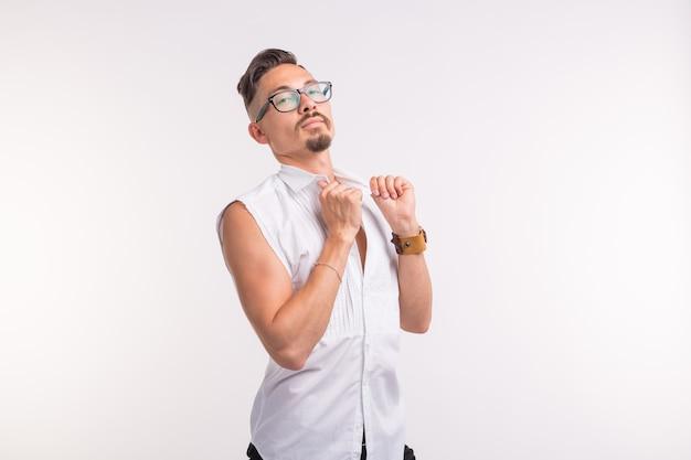 Jeune bel homme sexy posant en chemise blanche sur un mur blanc