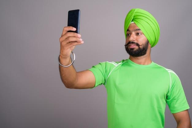 Jeune bel homme sikh indien prenant selfie avec téléphone mobile