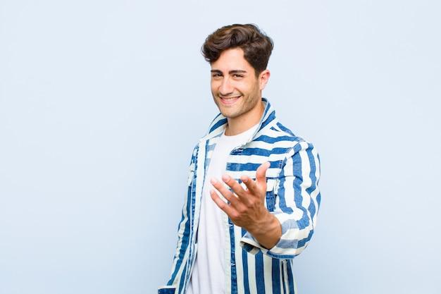 Jeune bel homme souriant, l'air heureux, confiant et sympathique, offrant une poignée de main pour conclure un accord, coopérant contre le mur bleu