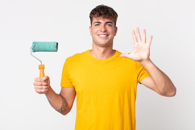 Jeune bel homme souriant et à l'air sympathique, montrant le numéro cinq. concept de maison de peinture