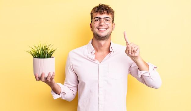 Jeune bel homme souriant et à l'air sympathique, montrant le numéro un. concept de plante décorative
