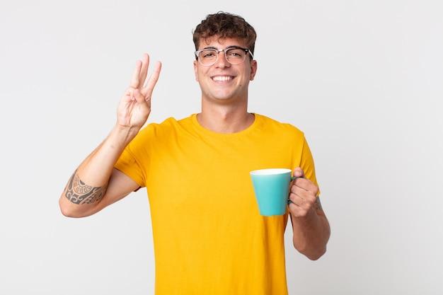 Jeune bel homme souriant et à l'air sympathique, montrant le numéro trois et tenant une tasse de café