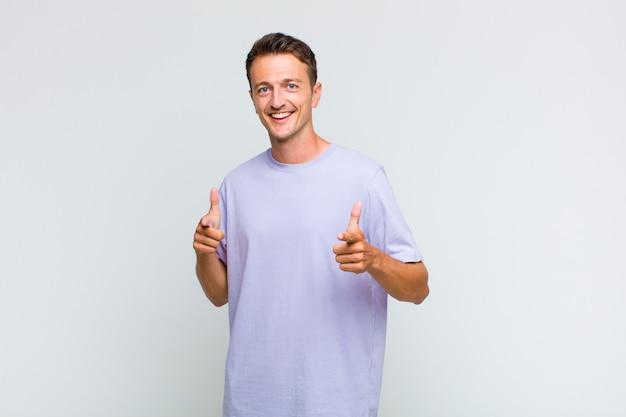 Jeune bel homme souriant avec une attitude positive, réussie et heureuse, pointant vers la caméra, faisant signe des armes à feu avec les mains