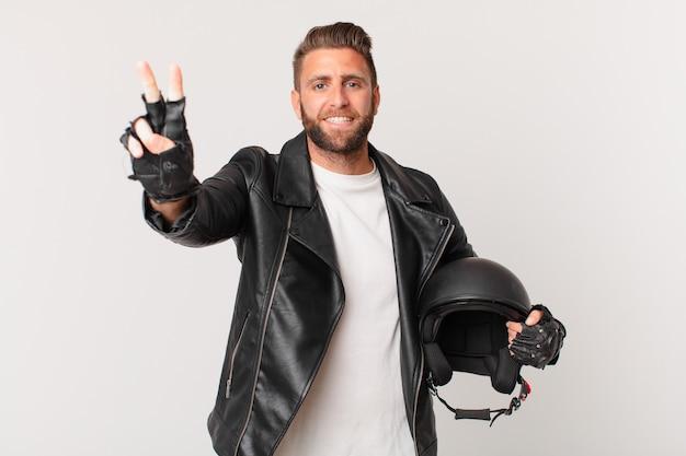 Jeune bel homme souriant et ayant l'air heureux, gesticulant la victoire ou la paix. concept de casque de moto