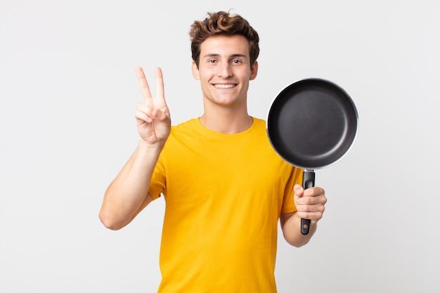 Jeune bel homme souriant et ayant l'air heureux, gesticulant la victoire ou la paix et tenant une casserole