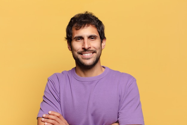 Jeune bel homme souriant avec les bras croisés