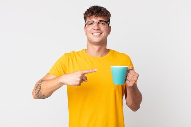 Jeune bel homme souriant gaiement, se sentant heureux et pointant vers le côté et tenant une tasse de café