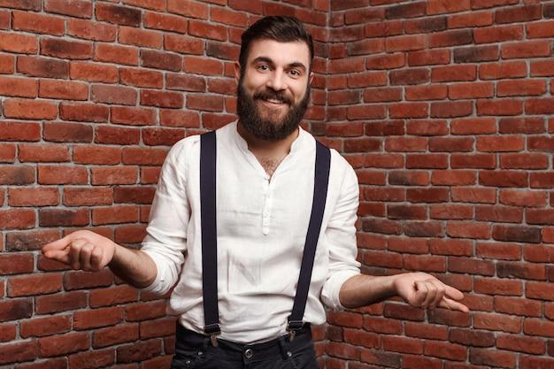 Jeune bel homme souriant gesticulant sur le mur de briques.